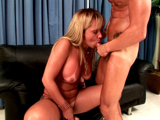 Busty blonde shemale in boots Dayanne wanking cock white giving oral sex on the couch